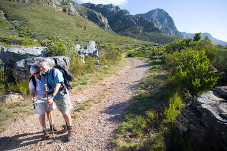 rucksacks: Mature couple, with rucksacks, hiking on mountain trail, looking at map, man leaning on hiking pole