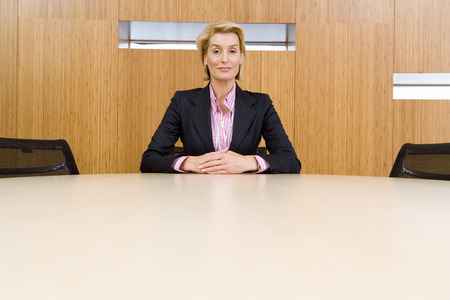 hands clasped: Businesswoman alone at conference table, hands clasped, portrait, low angle view LANG_EVOIMAGES