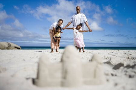 two generation family: Sandcastle on beach, focus on two generation family in background, portrait, surface level LANG_EVOIMAGES