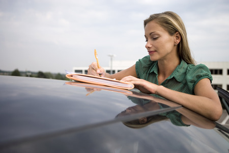roof profile: Blonde woman leaning on stationary car roof, writing on piece of paper in folder, smiling