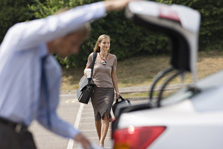 Man opening car boot in car park, focus on businesswoman walking with luggage in background, smiling