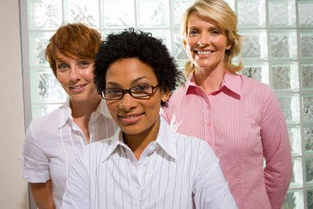 glass block: Three businesswomen standing by glass block wall, smiling, portrait, close-up