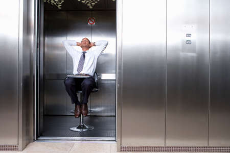 out of context: Mature businessman on stool in lift, laptop on lap, leaning back with head in hands LANG_EVOIMAGES