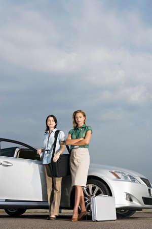 open car door: Two businesswomen standing beside open car door, smiling, portrait