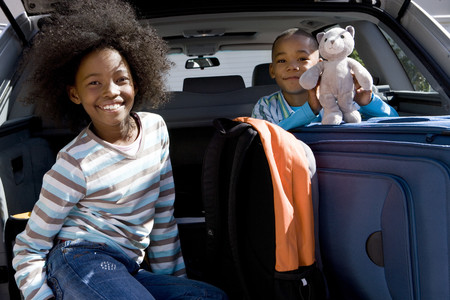 Brother and sister (6-10) in back of car with luggage, boy holding toy, smiling, portrait Imagens