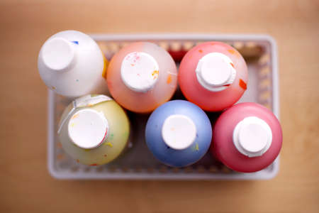 differential focus: Bottles of multi-coloured paints, close-up, overhead view (still life, differential focus) LANG_EVOIMAGES