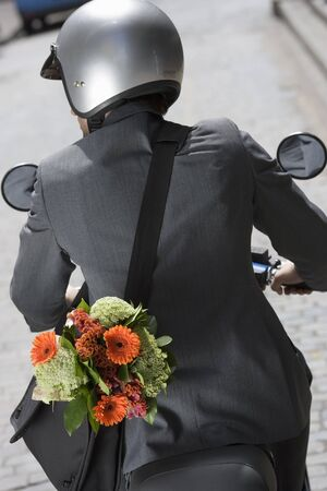 crash helmet: Man in crash helmet riding on scooter in street, carrying flower bouquet in bag, rear view (tilt)