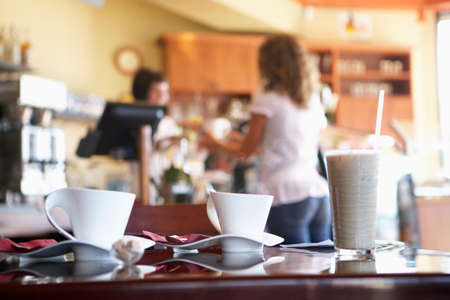 differential focus: Waitress serving female customer in cafe, focus on glass and coffee cups on table in foreground