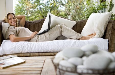differential focus: Woman lying on sofa with laptop, trees in background, bowl of pebbles in foreground, smiling, portrait (differential focus)