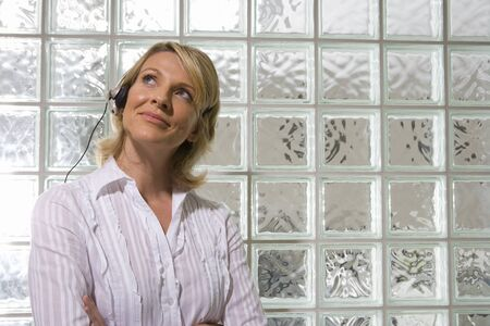 glass block: Businesswoman wearing headset by glass block wall, arms crossed, smiling, close-up