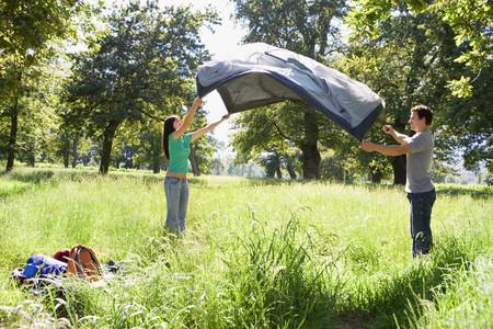 숲 비운의 캠핑 여행에 텐트를 조립 커플, 측면보기