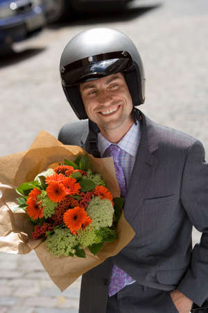 crash helmet: Man wearing crash helmet, standing in street, holding bouquet of flowers, smiling (tilt)