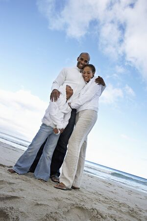 two generation family: Two generation family in white clothing embracing on beach, smiling, portrait, low angle view (tilt) LANG_EVOIMAGES