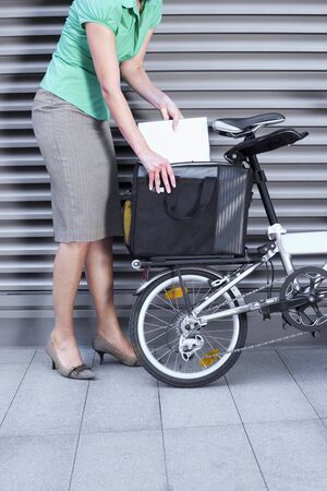 low section view: Businesswoman packing bag on the back of folding commuter bicycle, side view, low section LANG_EVOIMAGES