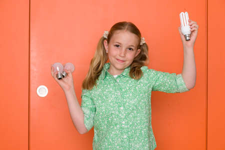 inefficient: Girl (9-11) holding up light bulbs by orange door and wall, smiling, portrait