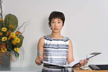 handsfree device: Young female receptionist with folder by flower arrangement, portrait LANG_EVOIMAGES