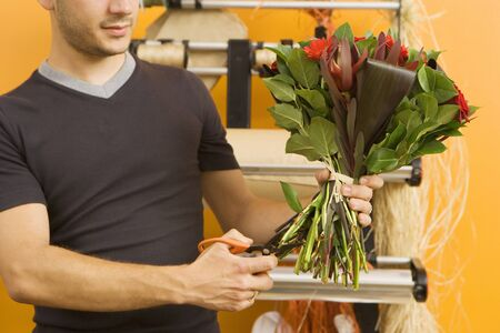 midsection: Male florist preparing bouquet of flowers in flower shop, cutting stems with scissors, mid-section