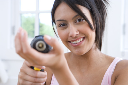 differential focus: Young woman using electric drill, smiling, portrait (differential focus)