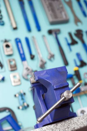 close up  wrench: Blue vice in front of display rack in tool shop, focus on foreground, low angle view (tilt)