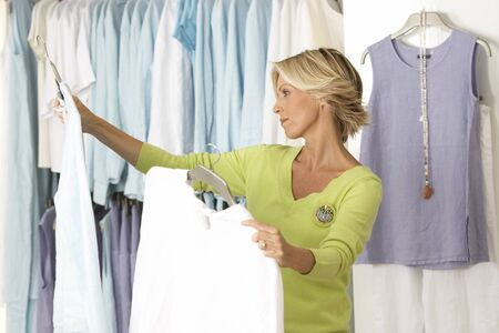 coathangers: Mature woman shopping in clothes shop, comparing two tops on coathangers, side view LANG_EVOIMAGES