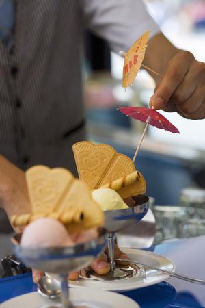 differential focus: Waiter preparing ice cream desserts, adding cocktail umbrellas, close-up (differential focus)