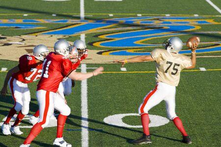 jugando futbol: Quarterback de fútbol americano de intentar lanzar la bola como los jugadores rivales en cerrar durante el partido, vista lateral competitiva
