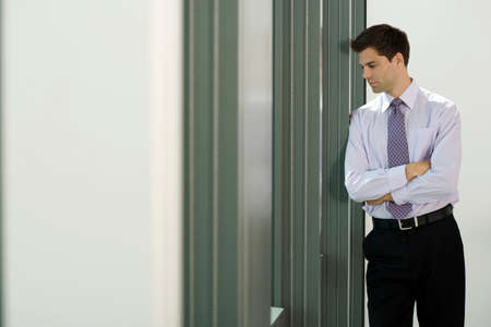 one mid adult man only: Businessman leaning against wall in office, looking through window, thinking, side view LANG_EVOIMAGES