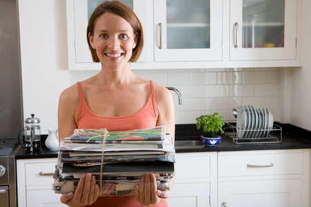 one mid adult woman only: Young woman with newspaper bundle in kitchen, smiling, portrait