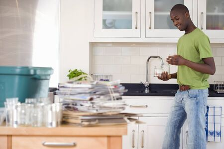 bundling: Young man rinsing jars in kitchen, recycling on side, smiling, side view