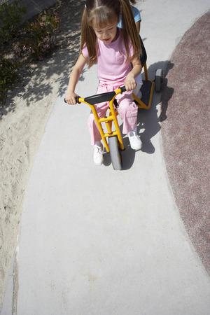 tilt view: Two girls (4-6) riding toy tricycle in playground, front view, elevated view (tilt)