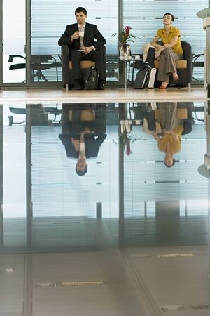 shiny floor: Businessman and businesswoman sitting in lobby, man holding cup, reflection on shiny floor