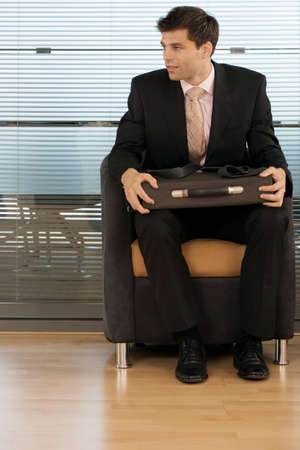 one mid adult man only: Businessman sitting in office chair, briefcase in lap