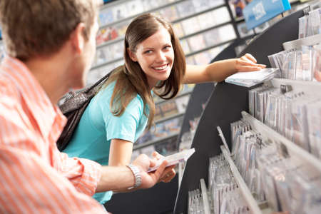 record shop: Young man passing CD to woman in record shop, bending down, smiling, side view, focus on background (tilt)