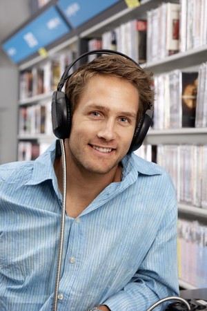 record shop: Young man wearing headphones, listening to CDs in record shop, smiling, close-up, portrait