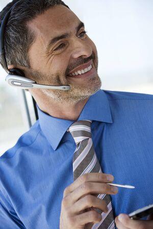 electronic organiser: Businessman wearing telephone headset, using personal electronic organiser, smiling, close-up (tilt)