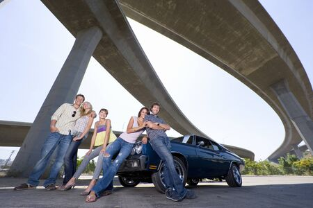 medium group: Medium group of friends on bonnet of car beneath overpass, smiling, portrait, low angle view LANG_EVOIMAGES