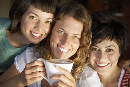 only three people: Three young women posing cheek to cheek in cafe, smiling, central woman holding cup of coffee, close-up, portrait (tilt)