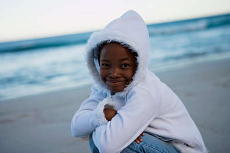 only girls: Girl (8-10) wearing white top with hood, crouching on beach at sunset, smiling, portrait (tilt)