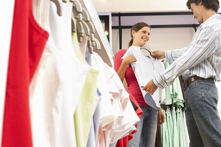 low blouse: Couple shopping in clothes shop, man holding pale blue top up against girlfriend, smiling, side view LANG_EVOIMAGES