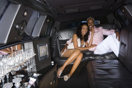 Young couple in limousine, smiling, portrait Imagens