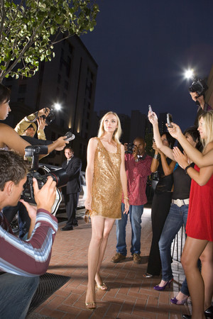 debutante: Young woman surrounded in people taking photographs, low angle view LANG_EVOIMAGES