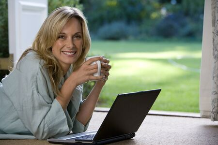 french doors: Woman lying on stomach by French doors holding mug by laptop, smiling, portrait