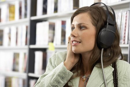 record shop: Young woman wearing headphones, listening to CDs in record shop, smiling, close-up, side view LANG_EVOIMAGES