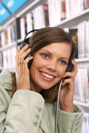 record shop: Young woman wearing headphones, listening to CDs in record shop, smiling, close-up LANG_EVOIMAGES