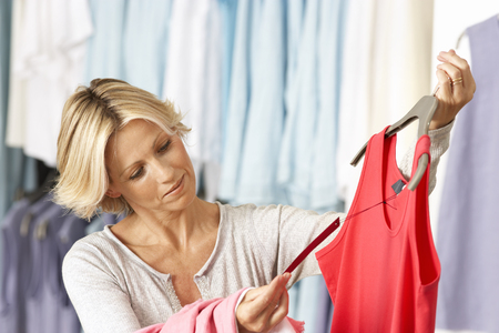 vest top: Mature woman shopping in clothes shop, holding red vest top on coathanger, checking price tag, smiling