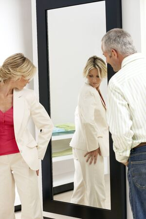 fitting room: Woman trying on new clothes in fitting room, looking at reflection in mirror, husband watching