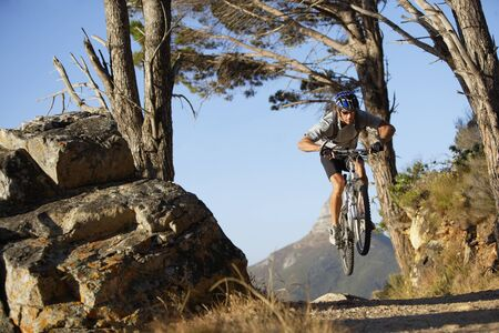 and south: South Africa, male mountain biker in mid-air over dirt track, front view