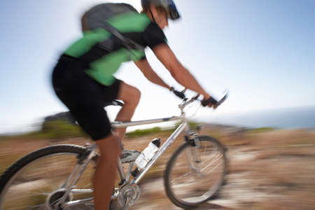 extreme terrain: Man mountain biking over extreme terrain, side view, sea in background (blurred motion) LANG_EVOIMAGES