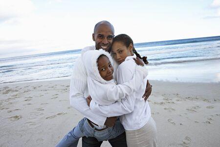 two generation family: Two generation family in white clothing embracing on beach, smiling, portrait (tilt)