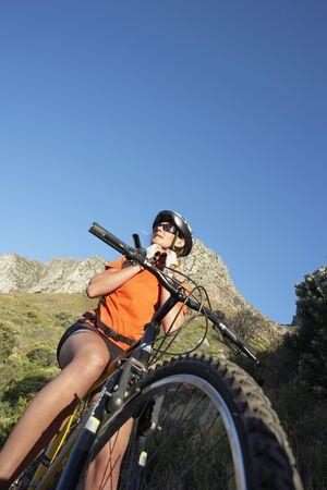 tilt view: South Africa, female mountain biker adjusting cycling helmet strap, low angle view (tilt)